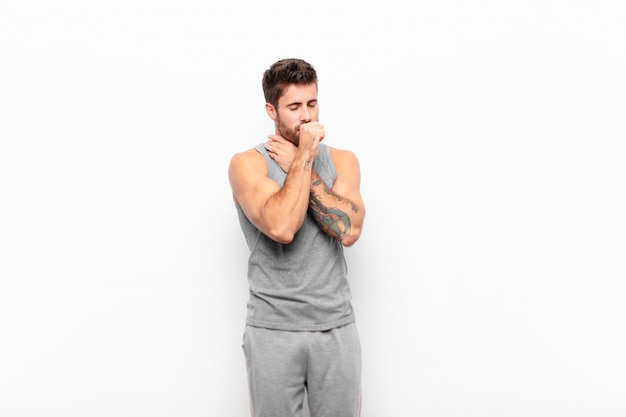 Jonge knappe man ziek met keelpijn en griepsymptomen, hoesten met kegelvormige mond. sport concept