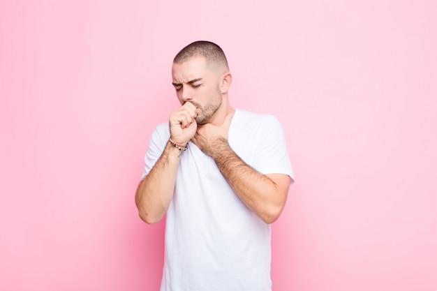 Jonge knappe man ziek voelen met een keelpijn en griep symptomen, hoesten met mond bedekt tegen platte muur