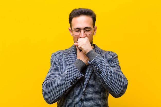 Jonge knappe man ziek voelen met een keelpijn en griep symptomen, hoesten met mond bedekt