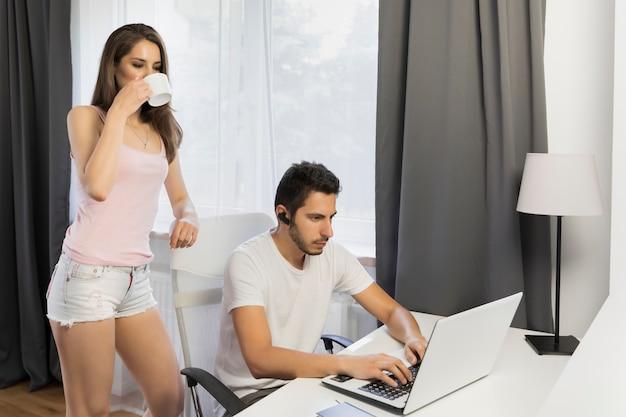 Jonge knappe man zit aan een tafel, ze werkt thuis op de computer. conceptuele foto over de levensstijl van freelancers.