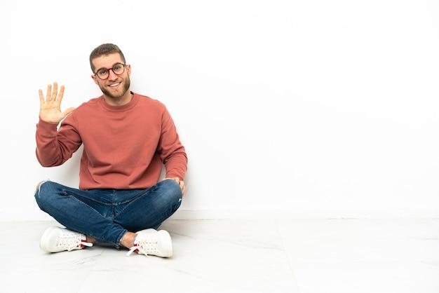 Jonge knappe man zittend op de vloer en telt vijf met vingers