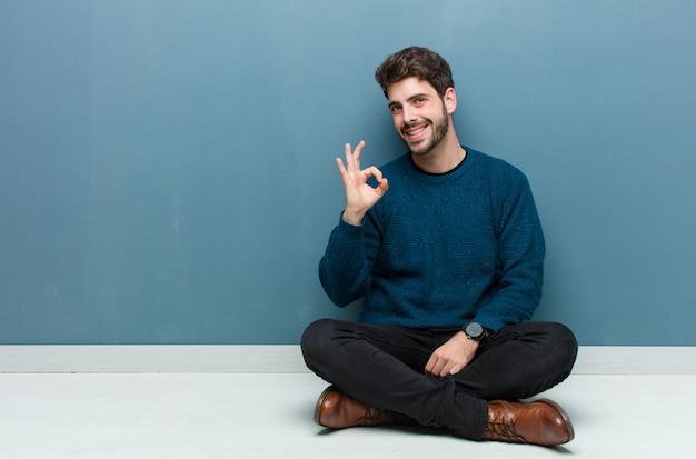 Jonge knappe man zittend op de vloer gelukkig, ontspannen en tevreden gevoel, goedkeuring tonen met goed gebaar, glimlachend