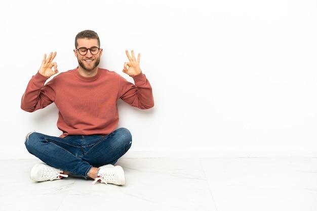 Jonge knappe man zittend op de vloer in zen pose