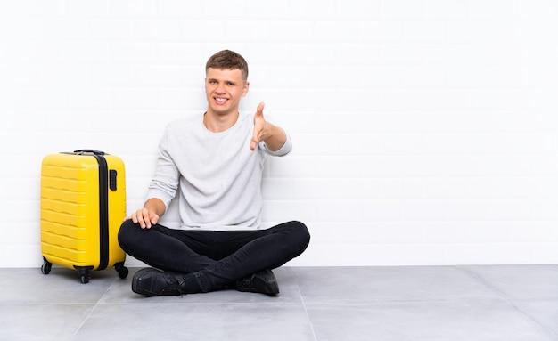 Jonge knappe man zittend op de vloer met een koffer handenschudden na goede deal