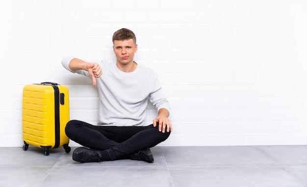 Jonge knappe man zittend op de vloer met een koffer met duim omlaag teken