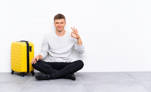 Jonge knappe man zittend op de vloer met een koffer met een ok bord met vingers