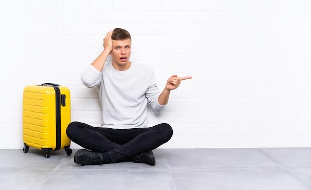 Jonge knappe man zittend op de vloer met een koffer verrast en wijzende vinger naar de kant