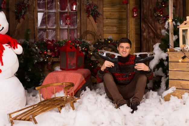 Jonge knappe man zittend op de vloer met katoenen sneeuw in de winter met schaatsen omringd door prachtige kerstdecors in het houten huis.