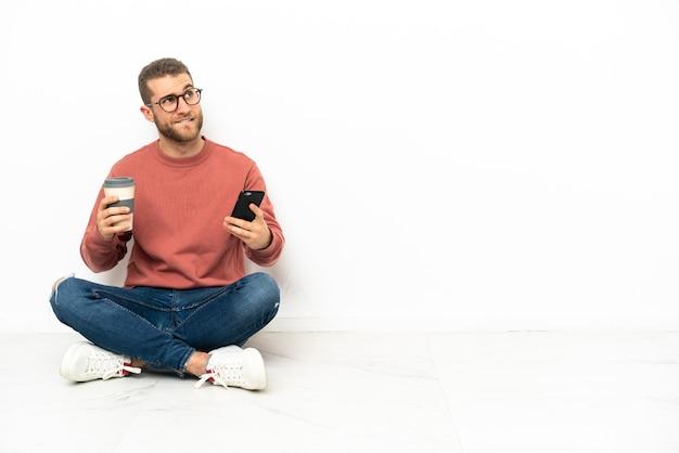 Jonge knappe man zittend op de vloer met koffie om mee te nemen en een mobiel terwijl hij iets denkt