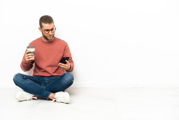 Jonge knappe man zittend op de vloer met koffie om mee te nemen en een mobiel
