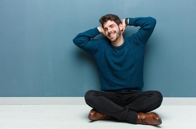 Jonge knappe man zittend op de vloer op zoek gelukkig, zorgeloos, vriendelijk en ontspannen genieten van het leven en succes, met een positieve houding