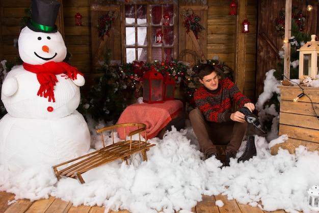 Jonge knappe man zittend op katoenen sneeuwdecor op de vloer terwijl hij schaatsen vasthoudt in een versierd houten huis met een grote wintersneeuwman.