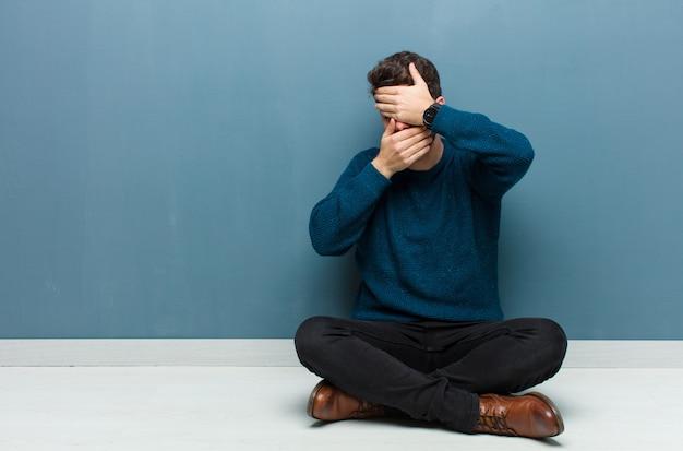 Jonge knappe man zittend op vloerbedekking gezicht met beide handen nee zeggen tegen de camera! afbeeldingen weigeren of foto's verbieden