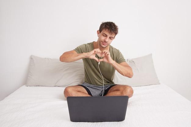 Jonge knappe man zittend op zijn bed op videogesprek met zijn laptop, hartsymbool maken met zijn handen. geliefd. kaukasisch.