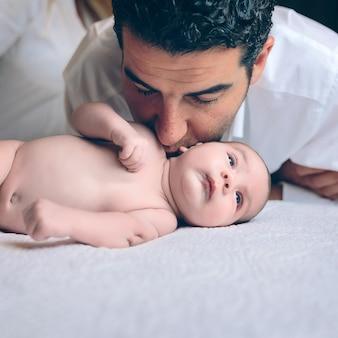 Jonge knappe man zoenen in de nek aan vreedzame pasgeboren liggend over een bed. vaderschap en babyverzorgingsconcept.