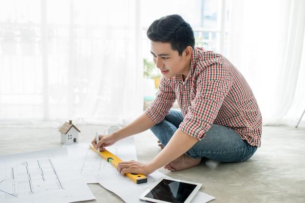 Jonge knappe mannelijke aziatische architect die thuis op de vloer werkt.