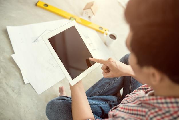 Jonge knappe mannelijke aziatische architect die thuis werkt met behulp van tablet op de vloer.