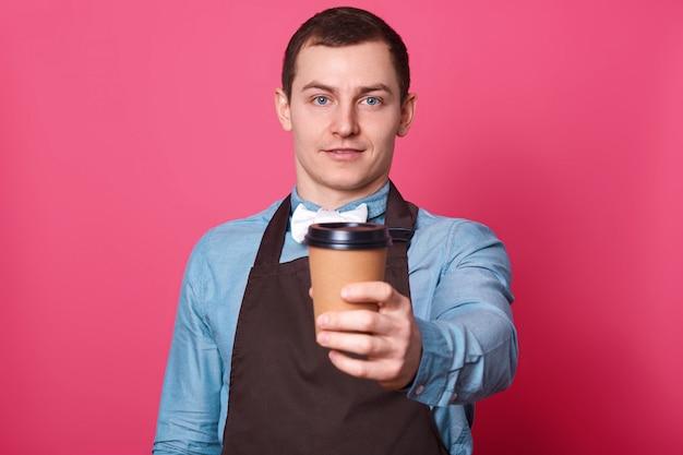 Jonge knappe mannelijke barista stelt voor dat je een kopje koffie van hem maakt, een witte vlinderdas en een bruin schort