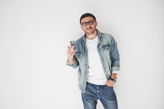 Jonge knappe mannelijke directeur die in toevallige kledij een creditcard houden