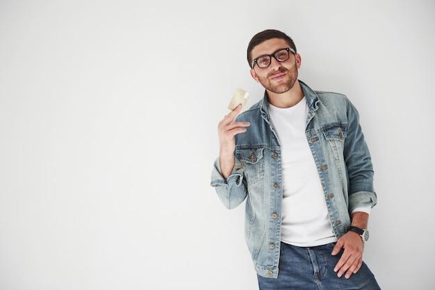 Jonge knappe mannelijke directeur die in toevallige kledij een creditcard in de zakken op wit houden