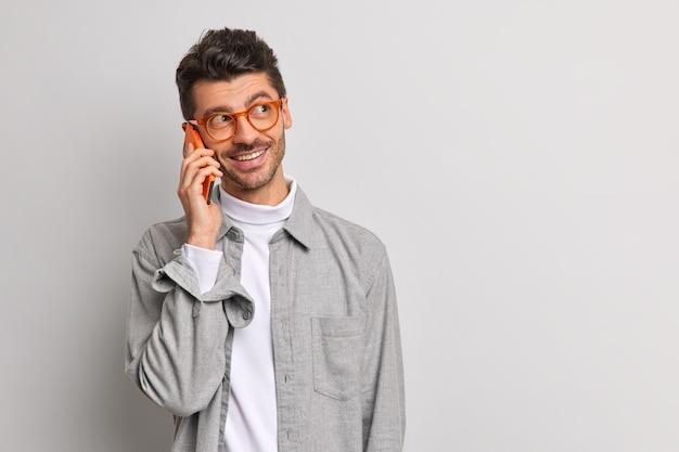 Jonge knappe mannelijke freelancer praat via mobiele telefoon heeft vrolijke uitdrukking geniet van mobiele tarieven en verbinding