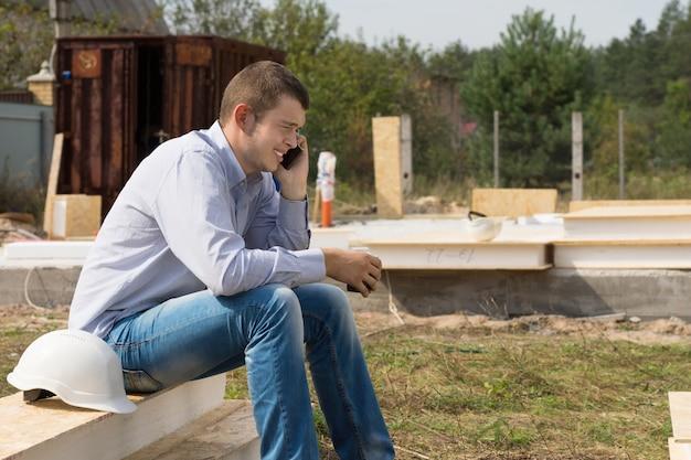 Jonge knappe mannelijke ingenieur die iemand praat via mobiele telefoon met witte helm aan de zijkant.