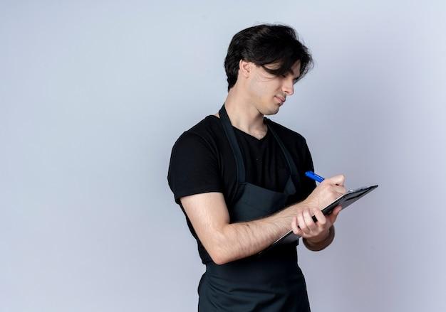 Jonge knappe mannelijke kapper in uniform schrijven iets op klembord geïsoleerd op wit