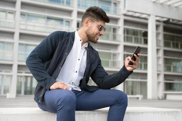 Jonge knappe mannen met smartphone in een stad glimlachende jonge man sms'en op zijn mobiele telefoon koffie b...
