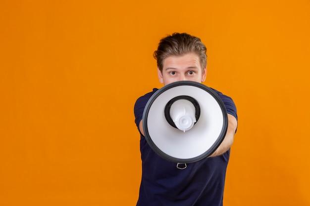 Jonge knappe mens die aan megafoon spreken die camera positieve en gelukkige status over oranje achtergrond bekijken
