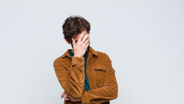 Jonge knappe mens die beklemtoond, beschaamd of verstoord, met hoofdpijn kijkt, die gezicht behandelt met hand tegen muur