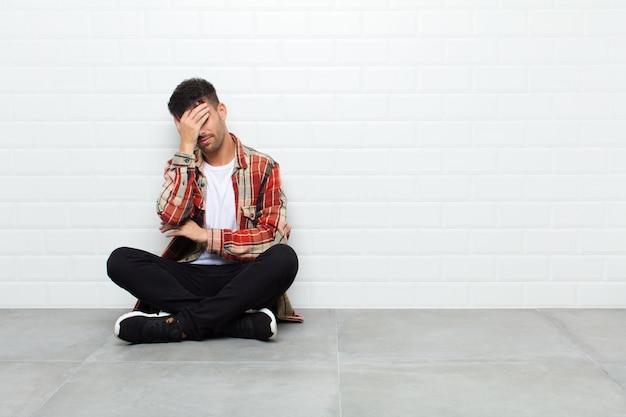 Jonge knappe mens die beklemtoond, beschaamd of verstoord, met hoofdpijn kijkt, die gezicht behandelt met handzitting op cementvloer