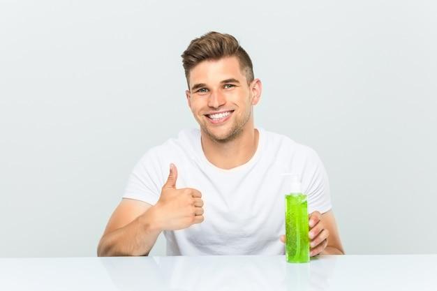 Jonge knappe mens die een fles houden van aloëvera die en duim glimlachen opheffen