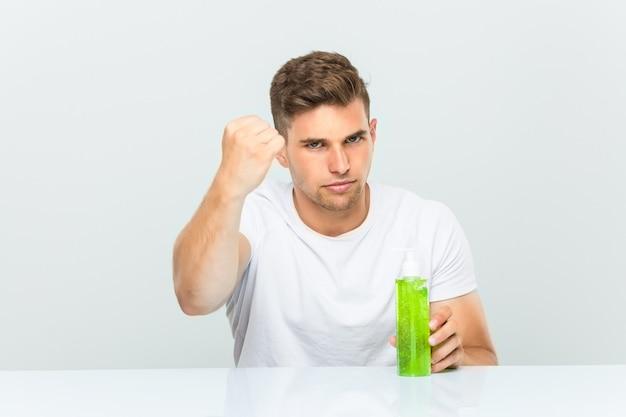 Jonge knappe mens die een fles van aloëvera houden die vuist tonen aan camera