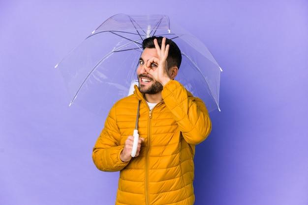 Jonge knappe mens die een paraplu opgewekt houden houdend ok gebaar op oog.