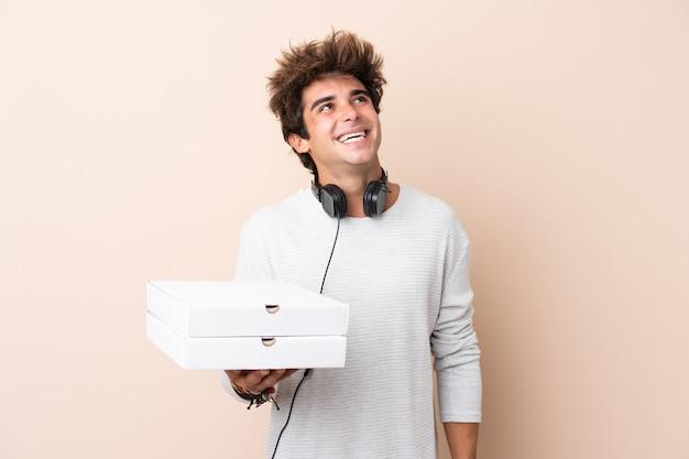 Jonge knappe mens die een pizza over geïsoleerde muur houdt die omhoog terwijl het glimlachen kijkt