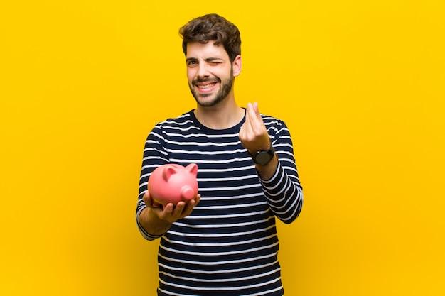 Jonge knappe mens die een spaarvarken houdt tegen sinaasappel backgroun