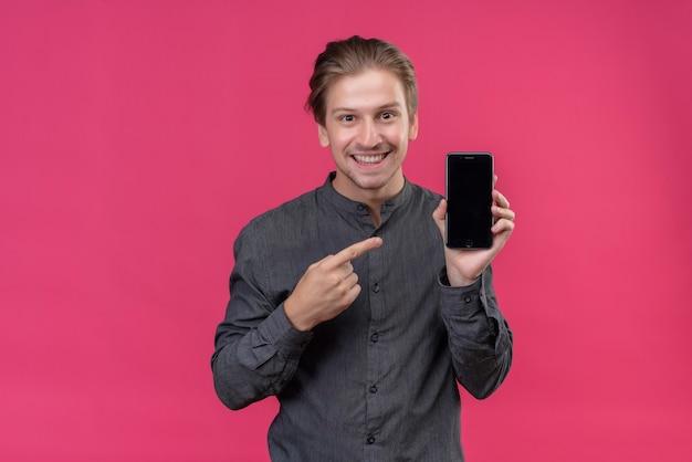 Jonge knappe mens die en mobiele telefoon houdt die met vinger ernaar wijst toont