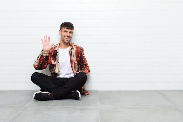Jonge knappe mens die gelukkig en vrolijk glimlacht, hand golft, u begroet en begroet, of afscheid zittend op cementvloer