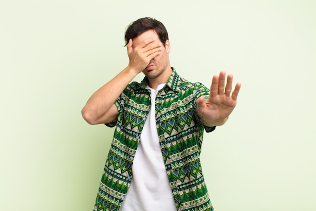 Jonge knappe mens die gezicht behandelen met hand en andere hand vooraan plaatsen om camera tegen te houden, foto's of afbeeldingen weigeren