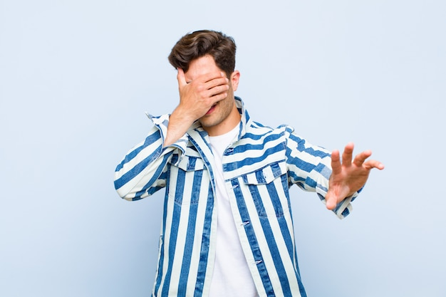 Jonge knappe mens die gezicht behandelt met hand en andere hand vooraan zet om camera tegen te houden, die foto's of beelden over blauwe muur weigert