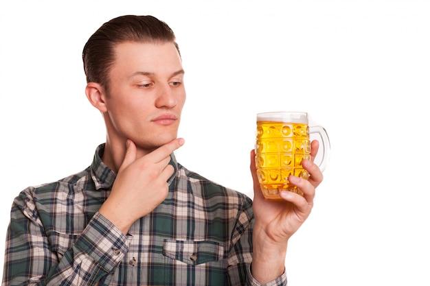 Jonge knappe mens die het glas bier met twijfel bekijken, dat op wit wordt geïsoleerd. aantrekkelijke man die glas bier onderzoekt
