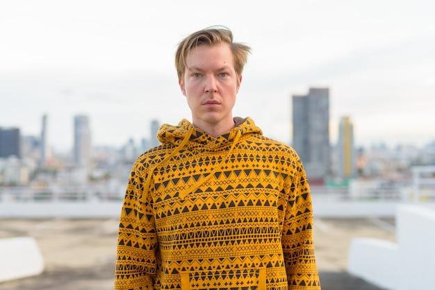 Jonge knappe mens die hoodie dragen tegen mening van de stad