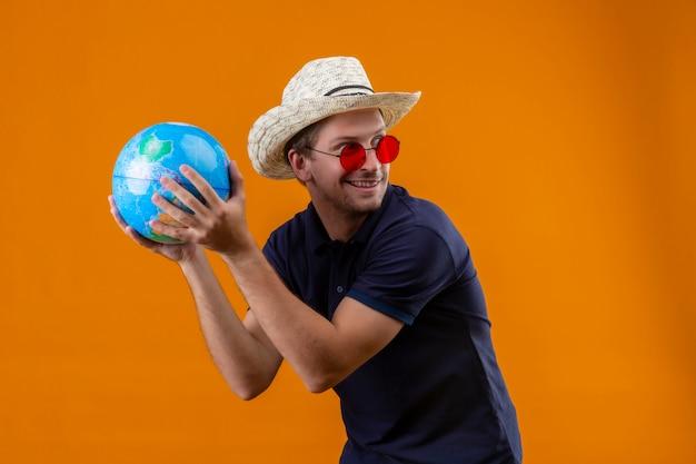 Jonge knappe mens die in de zomerhoed rode zonnebril dragen die bol houden kijkend opzij glimlachend sluw status over oranje achtergrond