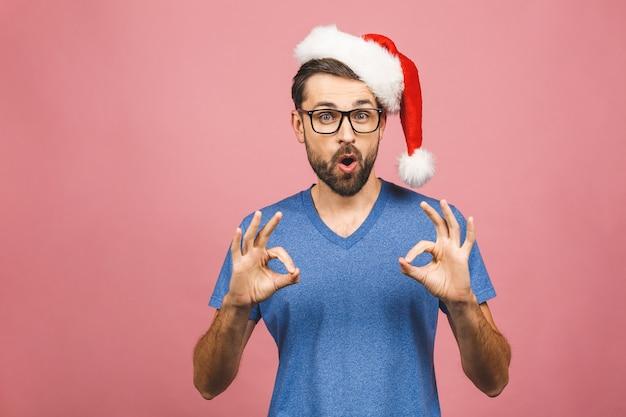 Jonge knappe mens die kerstmishoed dragen die positief doend ok teken met hand en vingers glimlachen. succesvolle expressie.