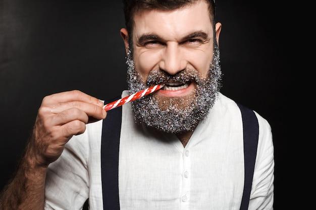 Jonge knappe mens die kerstmissuikergoed over zwarte eet.