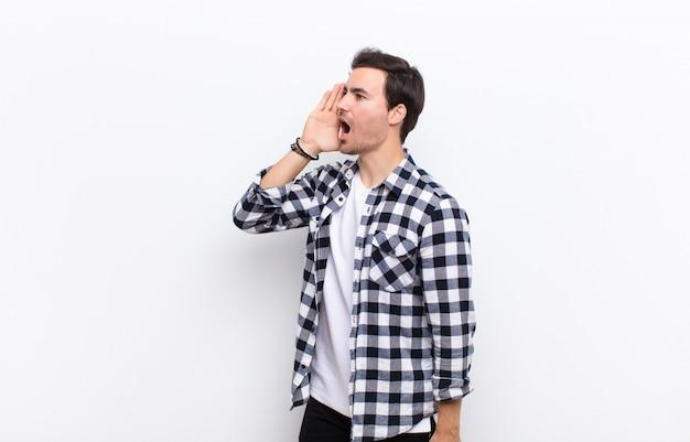 Jonge knappe mens die luid en boos schreeuwt om ruimte aan de kant te kopiëren, met hand naast mond over witte muur