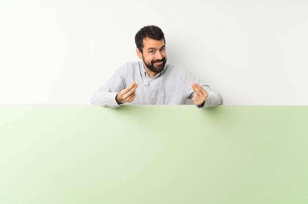 Jonge knappe mens die met baard een groot groen leeg aanplakbiljet houden die geldgebaar maken