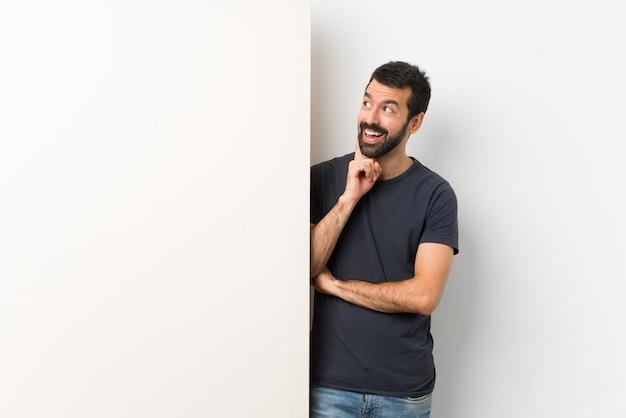 Jonge knappe mens die met baard een groot leeg aanplakbiljet houden die een idee denken terwijl omhoog het kijken