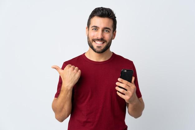 Jonge knappe mens die met baard mobiele telefoon met behulp van die op witte muur wordt geïsoleerd die aan de kant richt om een product te presenteren