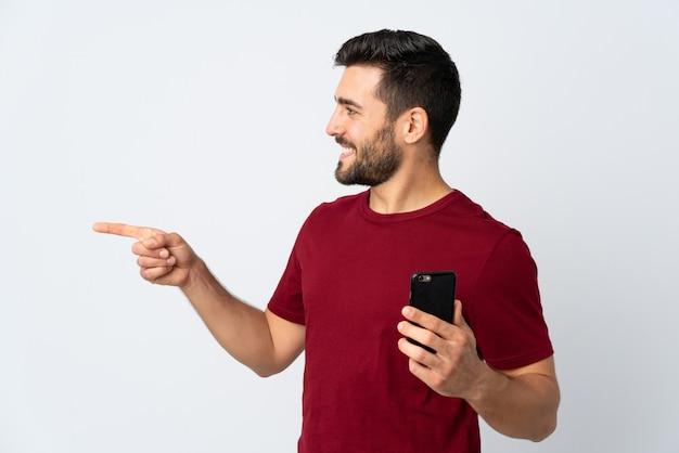 Jonge knappe mens die met baard mobiele telefoon op witte muur met behulp van die aan de kant richten om een product voor te stellen